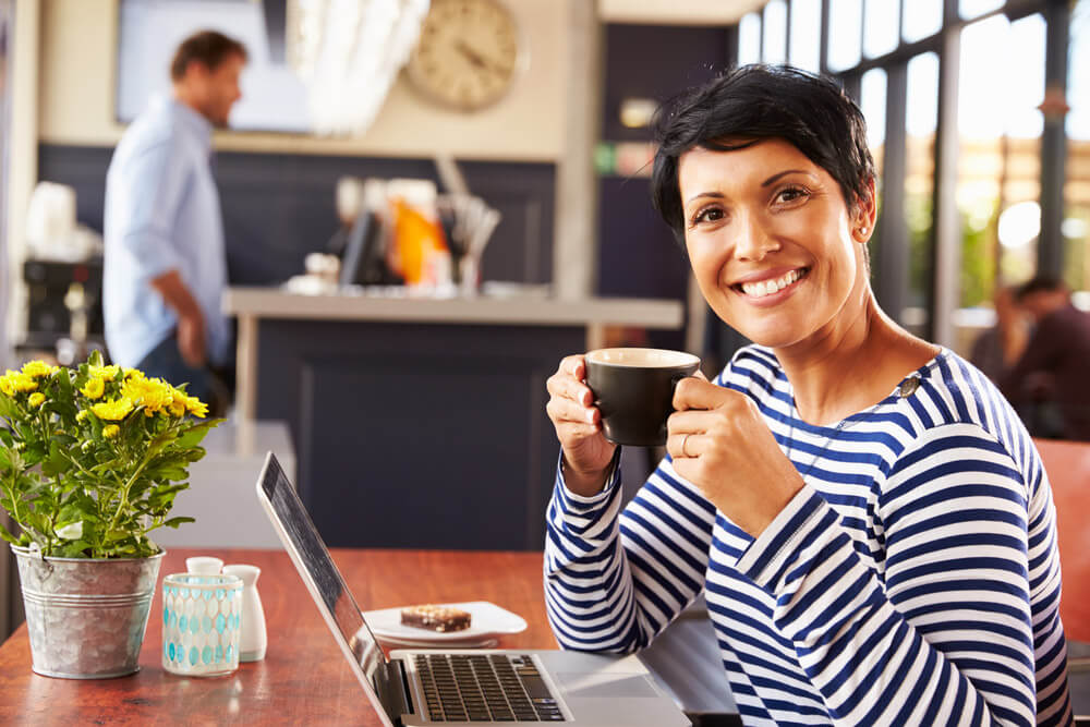 Woman enjoying a cup of coffee at a coffee house while looking at a laptop