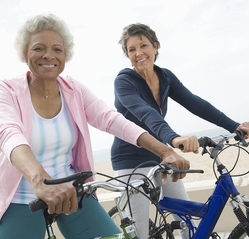 Two older women riding bikes on the beach